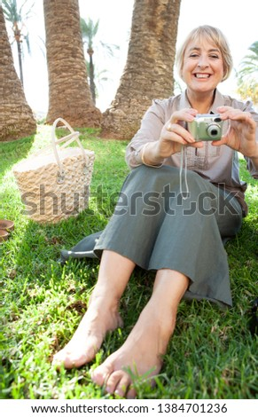 Beautiful mature woman sitting relaxing on grass park holding a digital photographic camera, smiling in sunny outdoors. Senior female tourist on holiday break, leisure technology lifestyle leisure.