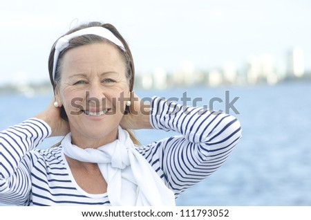 Beautiful mature woman standing relaxed at seaside, looking confident and happy, isolated with sky  and water as background and copy space.