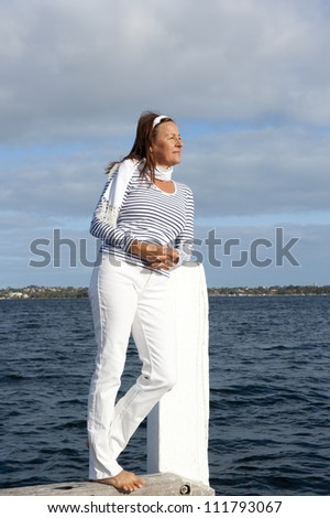 Beautiful mature woman standing relaxed at seaside, looking confident and happy, isolated with sky, water and coastline  as background and copy space.