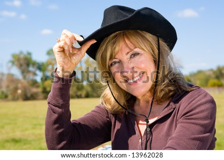 stock photo : Beautiful mature woman tipping her cowboy hat on a farm.