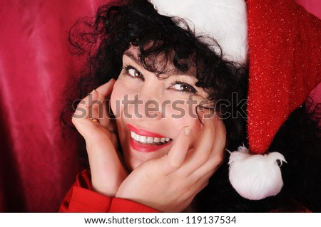 Beautiful mature woman wearing a Christmas hat and smiling