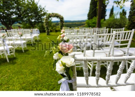 Beautiful meadow wedding venue. White chairs and wedding flowers arch. Nobody in the place.