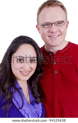 Beautiful Mexican wife and her clean cut American husband looking at camera happily. - stock photo