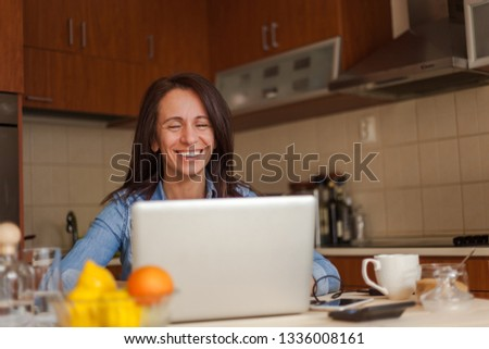 Beautiful mid adult woman enjoying morning routine while working on laptop in kitchen #1336008161