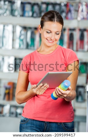 Beautiful mid adult woman scanning product\'s barcode through digital tablet in hardware store