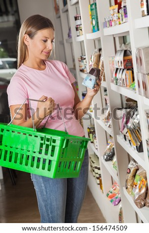 Beautiful mid adult woman with shopping basket choosing product in grocery store