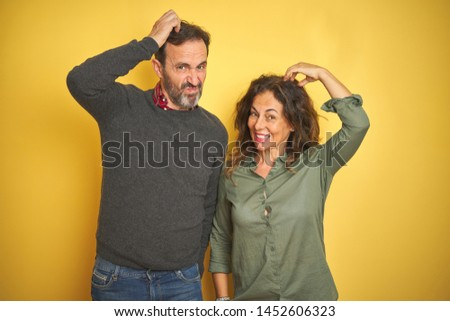 Beautiful middle age couple over isolated yellow background confuse and wonder about question. Uncertain with doubt, thinking with hand on head. Pensive concept.