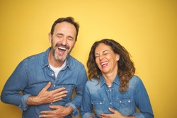 Beautiful middle age couple together standing over isolated yellow background smiling and laughing hard out loud because funny crazy joke with hands on body.