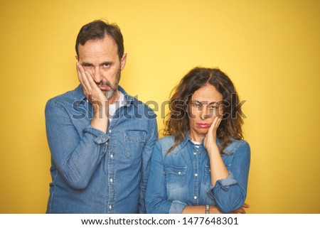 Beautiful middle age couple together standing over isolated yellow background thinking looking tired and bored with depression problems with crossed arms. Сток-фото ©