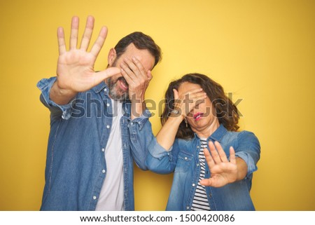Beautiful middle age couple together wearing denim shirt over isolated yellow background covering eyes with hands and doing stop gesture with sad and fear expression. Embarrassed and negative concept.