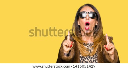Beautiful middle age elegant woman wearing sunglasses and mink coat amazed and surprised looking up and pointing with fingers and raised arms. #1415051429