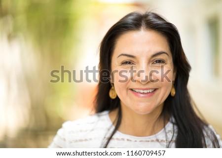 Beautiful middle age Hispanic woman smiling outside.