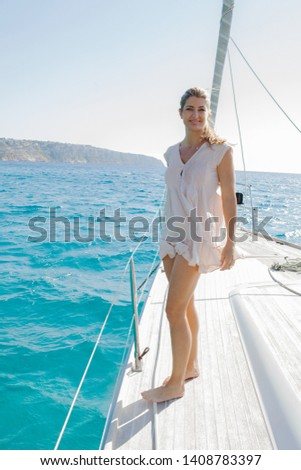 Beautiful middle age woman standing contemplating on luxury sailing yacht deck on sunny summer holiday, outdoors. Elegant female enjoying cruise on private boat, active leisure recreation lifestyle. #1408783397