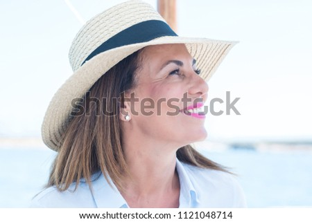 Beautiful middle age woman traveling on sailboat and smiling happy and confident.