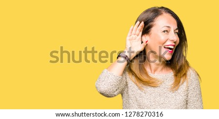 Beautiful middle age woman wearing fashion sweater smiling with hand over ear listening an hearing to rumor or gossip. Deafness concept.