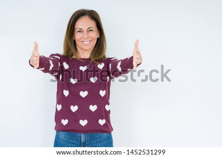 Beautiful middle age woman wearing heart sweater over isolated background looking at the camera smiling with open arms for hug. Cheerful expression embracing happiness.