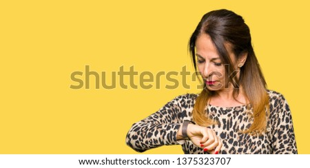 Beautiful middle age woman wearing leopard animal print dress Checking the time on wrist watch, relaxed and confident