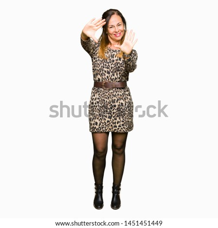 Beautiful middle age woman wearing leopard animal print dress Smiling doing frame using hands palms and fingers, camera perspective
