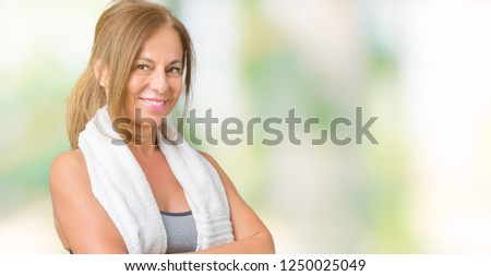 Beautiful middle age woman wearing sport clothes and a towel over isolated background happy face smiling with crossed arms looking at the camera. Positive person. #1250025049