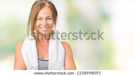 Beautiful middle age woman wearing sport clothes and a towel over isolated background skeptic and nervous, disapproving expression on face with crossed arms. Negative person. #1238998093