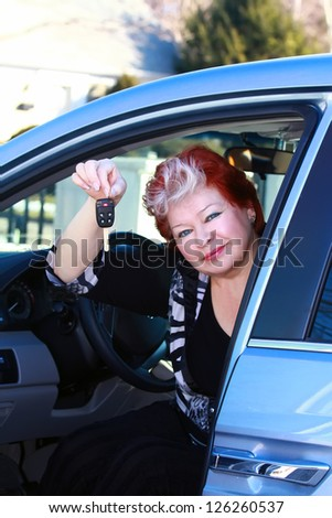 Beautiful middle age women sitting in the car and holding the car keys