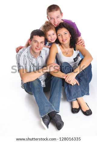 Beautiful middle aged couple carrying cute kids and smiling over white background