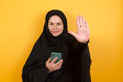Beautiful middle aged muslim woman wearing black hijab over yellow background using and texting with smartphone with open hand doing stop sign with serious and confident expression, defense gesture