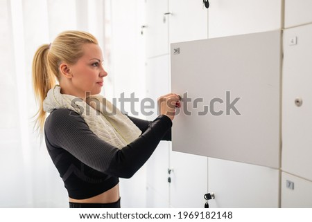 Beautiful middle aged sportswoman standing in the locker room and taking her clothes out of the locker after a workout at the gym. Foto stock ©
