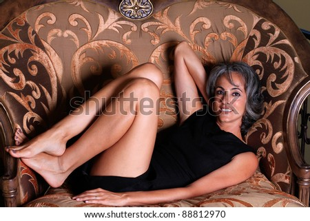 Beautiful Middle aged Woman curled up in a big chair after a night out