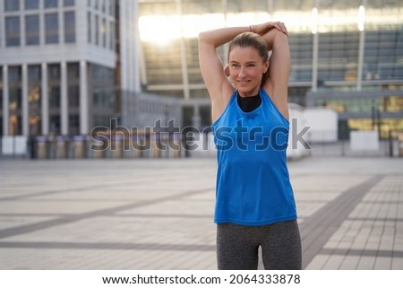 Beautiful middle aged woman in sportswear smiling while stretching her arms, standing outdoors, ready for workout in the city