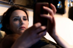 beautiful middle-aged woman looking at the smart phone lying on a couch at home tired carrying her baby at night.
