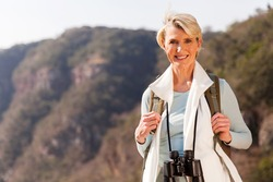 beautiful middle aged woman on top of the mountain with binoculars
