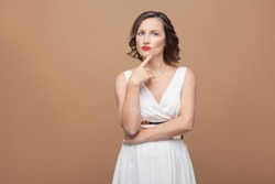 Beautiful middle aged woman thinking and puzzled. Emotional expressing woman in white dress, red lips makeup and dark curly hairstyle. Studio shot, indoor, isolated on beige or light brown background