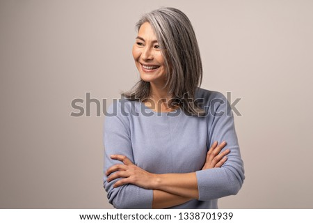 Beautiful Middle-Aged Woman With Crossed Arms Looks Aside. Charming Elderly Asian Woman With Crossed Arms Smiles While Looking Sideways.