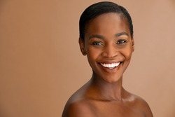Beautiful middle aged woman with perfect skin looking at camera against a brown background. Portrait of black beauty woman smiling in studio with smooth complexion flawless skin. Mature african lady.