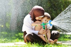 Beautiful Middle Eastern Arabic girl having baby playing with water sprinkler in garden