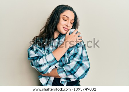 Beautiful middle eastern woman wearing casual clothes hugging oneself happy and positive, smiling confident. self love and self care  Foto stock ©