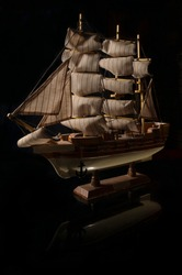 Beautiful miniature ship. Wooden ship figurine. Antique model sailing ship isolated with clipping path. Model of ship with sails on black background