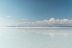 Beautiful mirror reflection on blue sky and cloud on Bolivia's Salt Flats. Shot in Salar de Uyuni salt flat. Water reflection of clouds and empty space. Holiday, vacation, freedom scene with horizon.