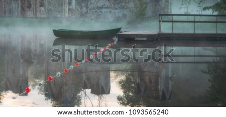 Beautiful misty lake with boat pier and green boat next to it #1093565240