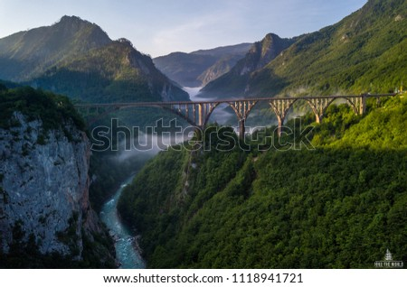 Beautiful misty morning view of Djurdjevica bridge over the river Tara in Montenegro, Europe. Beautiful world of Mediterranean countries. Aerial panorama.