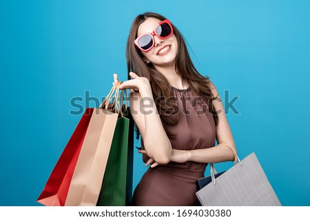 Beautiful mix race caucasian asian woman are holding shopping bags with face happily in blue seamless,isolated background. Shopping lifestyle, online shopping, promotion presenter concept.