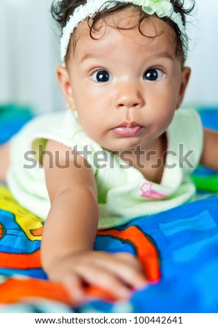 Beautiful mixed race baby girl lying in bed and looking at the camera - stock photo