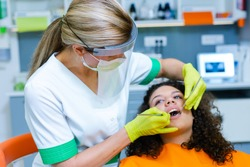 Beautiful mixed-race teenage girl on dental checkup by middle-age caucasian woman wearing face mask and visor as Coronavirus safety precaution. Modern dentist's office.