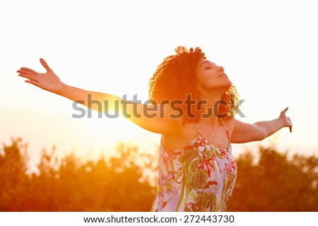Beautiful mixed race woman expressing freedom on a summer evening outdoors with her arms outstretched