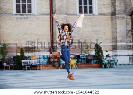 Beautiful mixed race young woman with curly hair jumping outdoors and holding map in hands. Globetrotter.