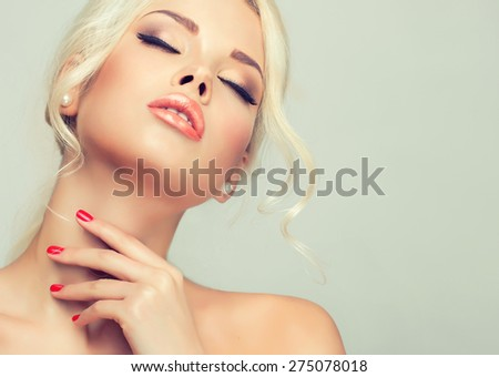 Beautiful model blonde with retro hair , bouffant hair, and a bushy tail . Hair style like Brigitte Bardot . Red nails manicure