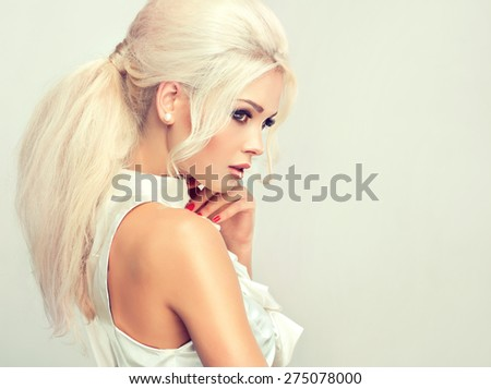 Beautiful model blonde with retro hair , bouffant hair, and a bushy tail . Red nails manicure and white blouse