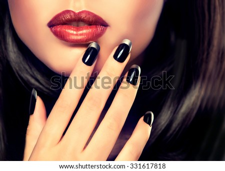 Beautiful model brunette shows black and silver French manicure on nails. Luxury fashion style, manicure, cosmetics and makeup .