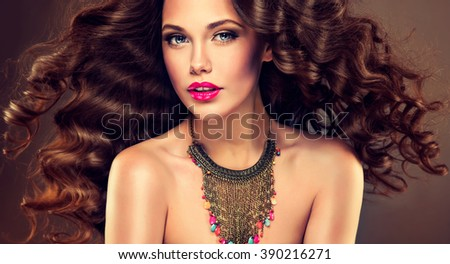 Beautiful model brunette with long curled hair and jewelry necklace .  Hairstyle small Curling